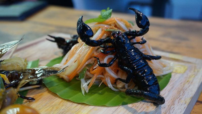 Eat a Scorpion salad at Bugs Cafe